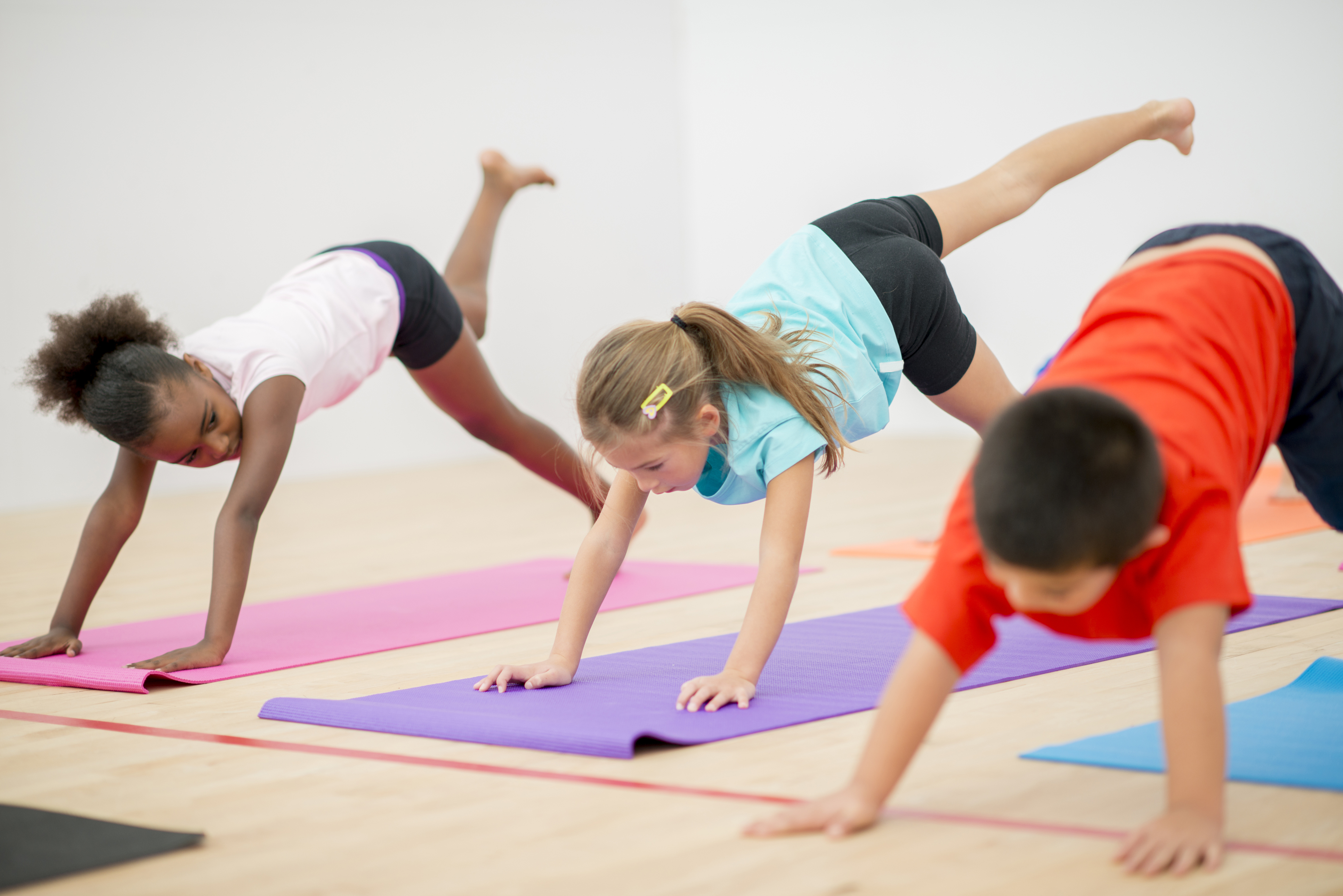Primary school children doing yoga on a mat