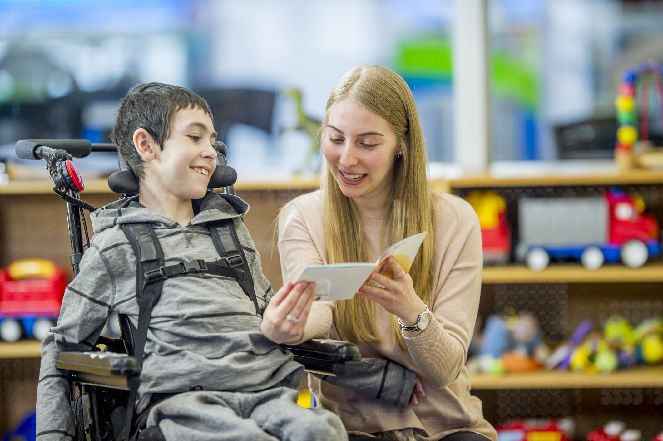 Teacher reading to a boy in a wheelchair
