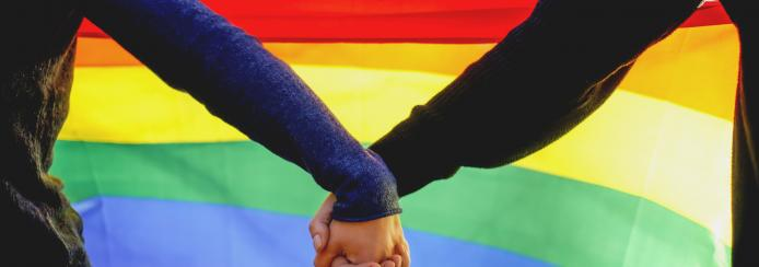 Two lesbian girls holding hands and rainbow flag