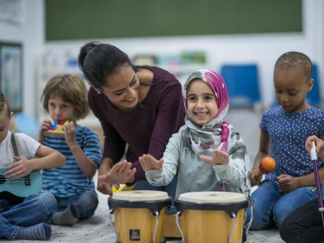 primary teacher with girl playing bongos