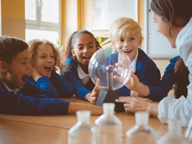Female teacher showing plasma ball during lesson at school
