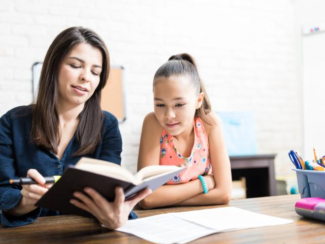 Student Listening To Teacher Reading Book At Table