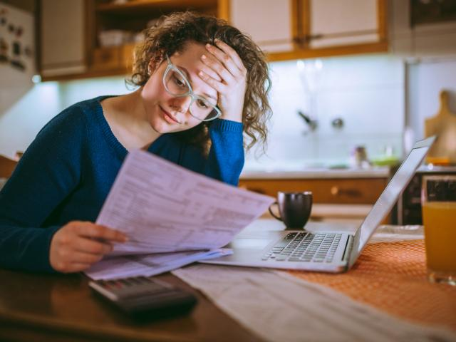 Worried woman holding bills