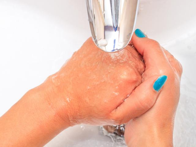 Female hands under running water in the sink