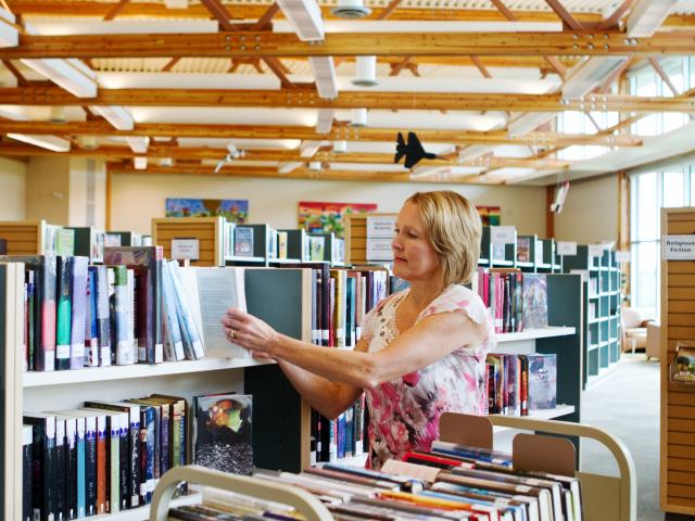 Librarian replacing books on shelves