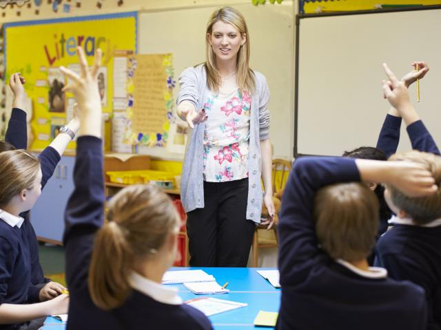 Teacher pointing to students with raised hands