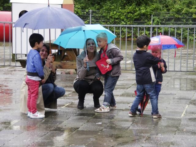 Parents and children with umbrellas in the rain