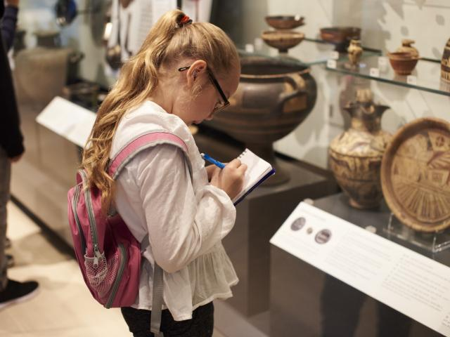 Girl looking at Greek vases in museum