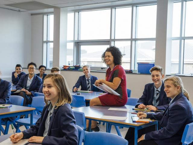 Teacher laughing with secondary school pupils