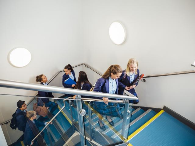 Secondary school children walking up stairs