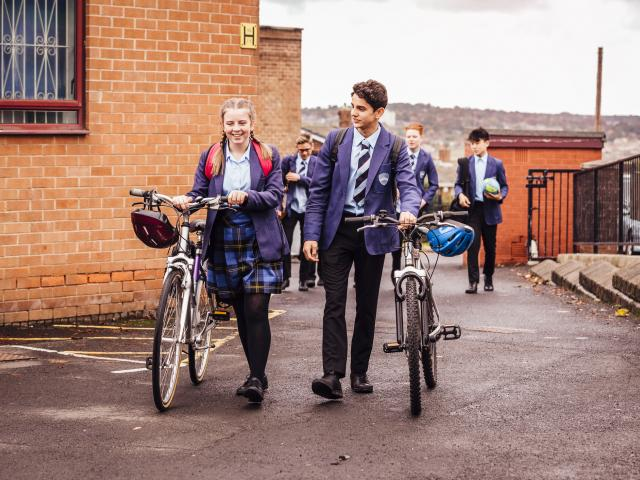 Secondary pupils in uniform pushing bikes