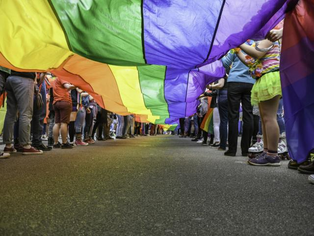 People holding LGBTQ flag