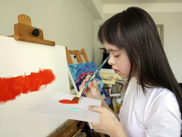 Girl with special educational needs painting