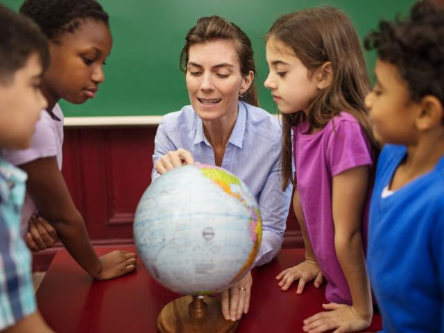 Teacher explaining globe to students in classroom
