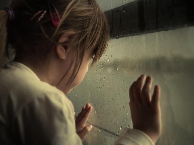 small girl looking out of rainy window