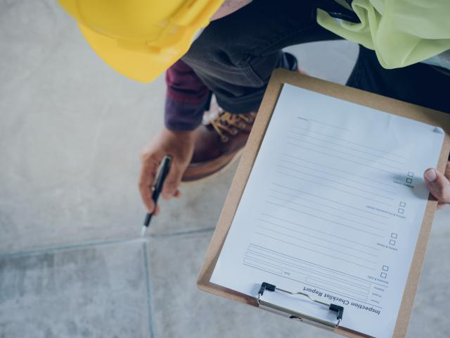 Man in hard hat with checklist on clipboard