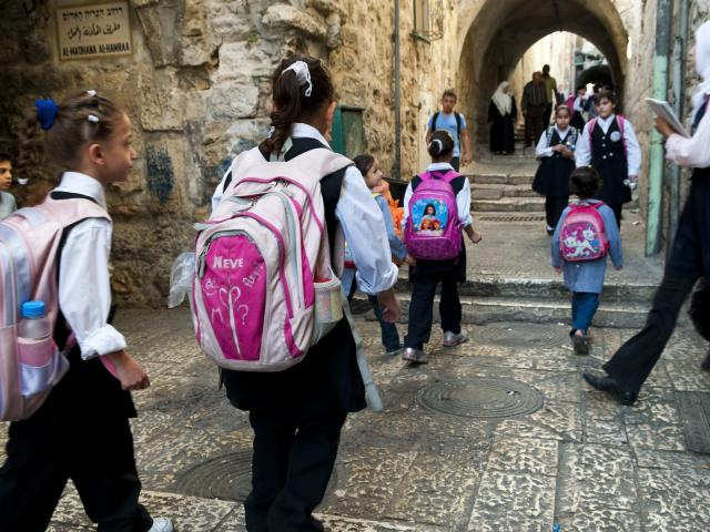 Palestinian schoolchildren walking through the street towards school